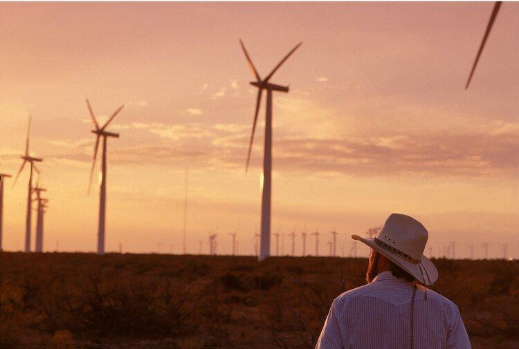cowboy looking at turbines